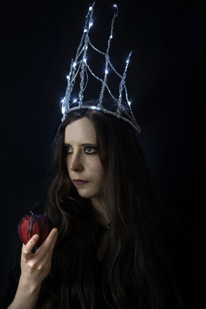 Autoportrait : La reine noire et sa pomme empoisonnée coiffée d'une haute couronne illuminée.