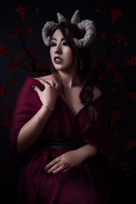 Hélène, démon romantique, regarde vers le passé, ses yeux noirs luisants dans la nuit. Photographie de portrait en studio.