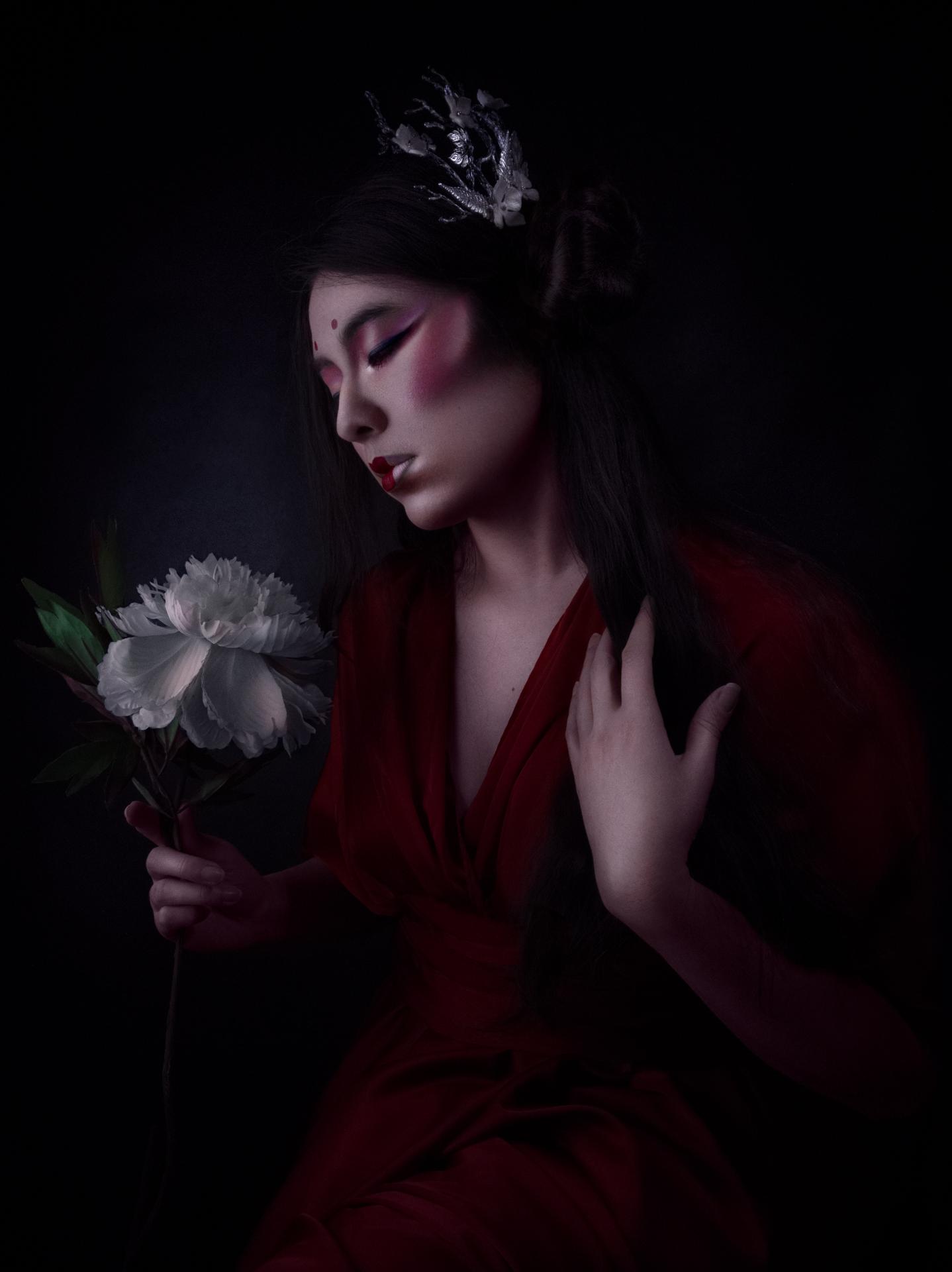 Triptyque : La geisha habillée de rouge. Elle se tient de profil. Un peigne est fixé dans sa longue chevelure. Les yeux clos, elle semble pourtant contempler une fleur blanche.