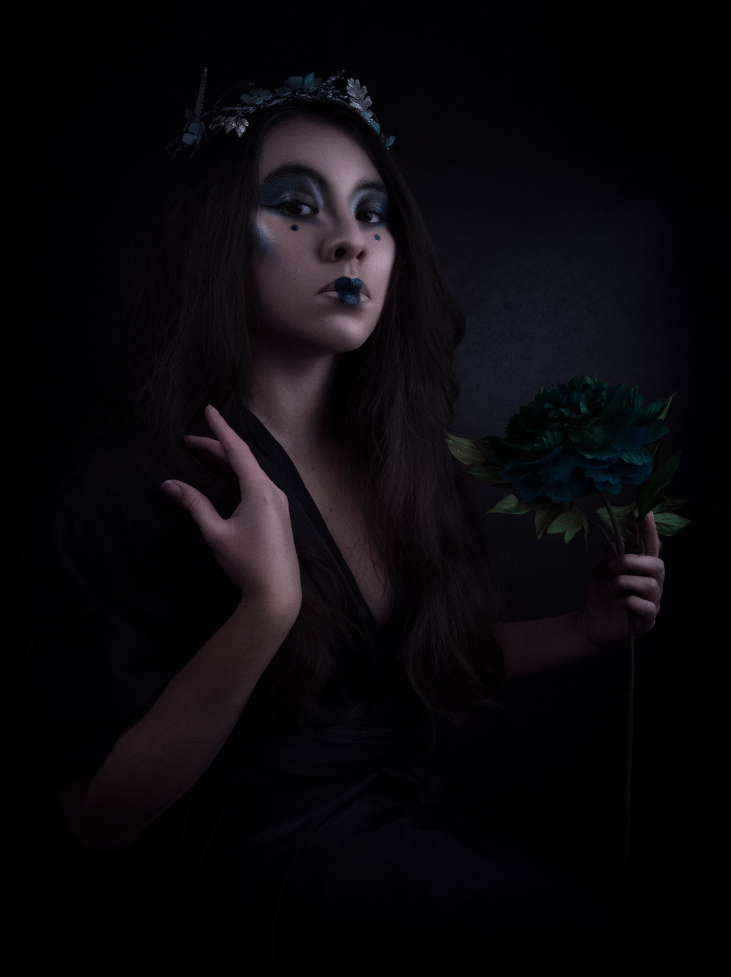 Triptyque : La geisha habillée de bleu. Elle nous regarde et tient une fleur dans la main gauche. Sa main droite est délicatement posée sur son épaule.