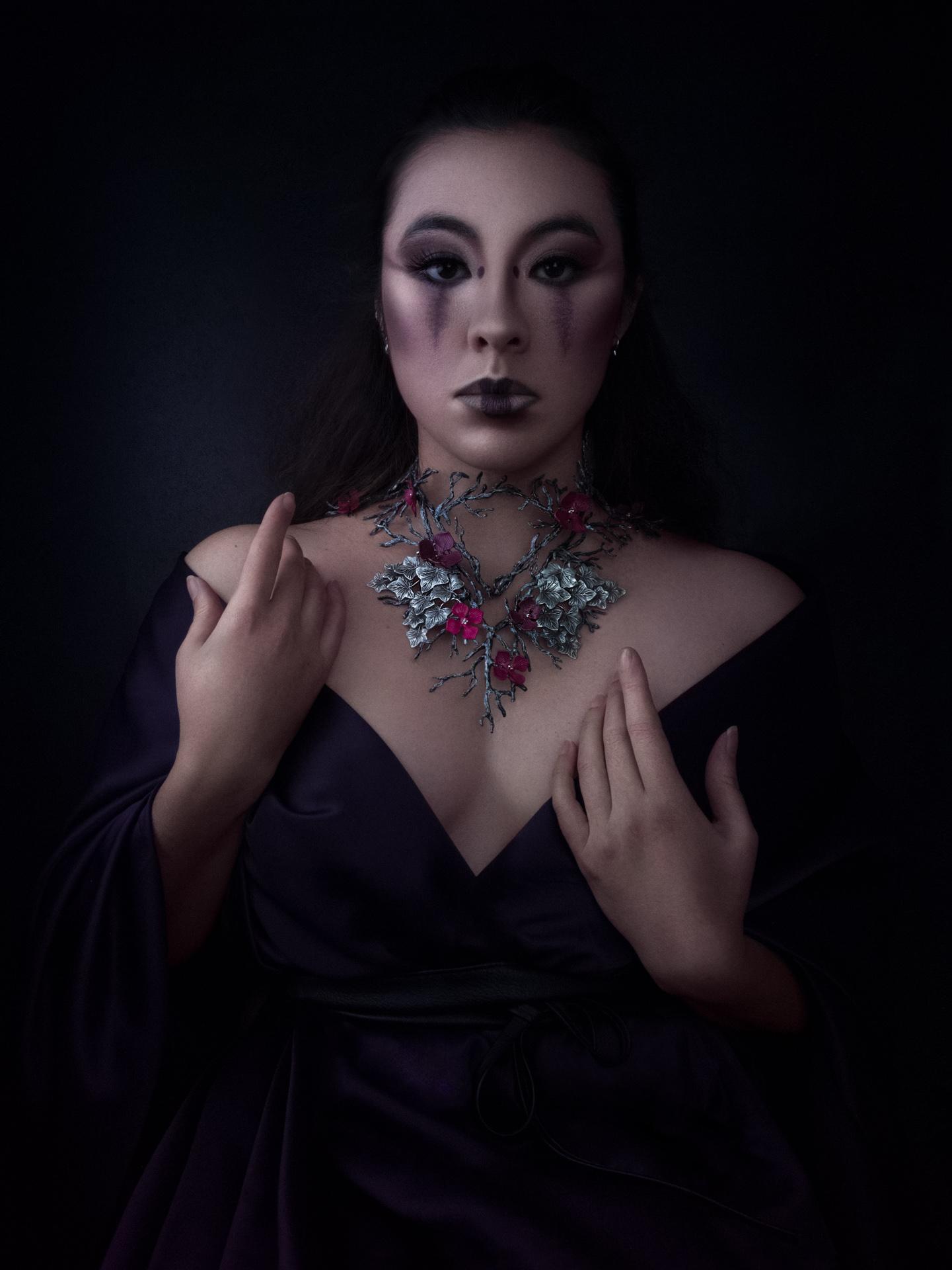 Triptyque : La geisha habillée de violet. Elle porte un magnifique collier de branches parsemé de fleurs rouges. Elle se tient face à nous, les mains posées dans une position biblique.