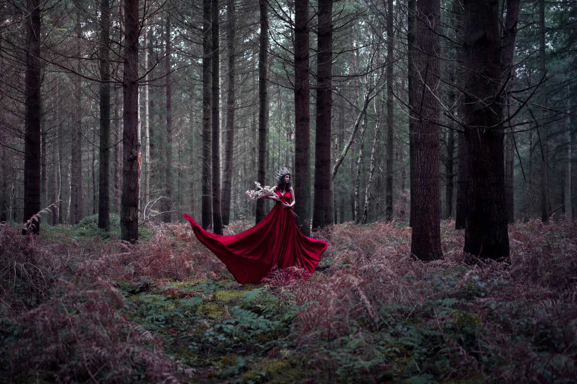 Marie se trouve au coeur d'une sombre forêt. Elle porte la grande robe rouge, flottant au vent, créée par les petits doigts de fée de Made by LN.