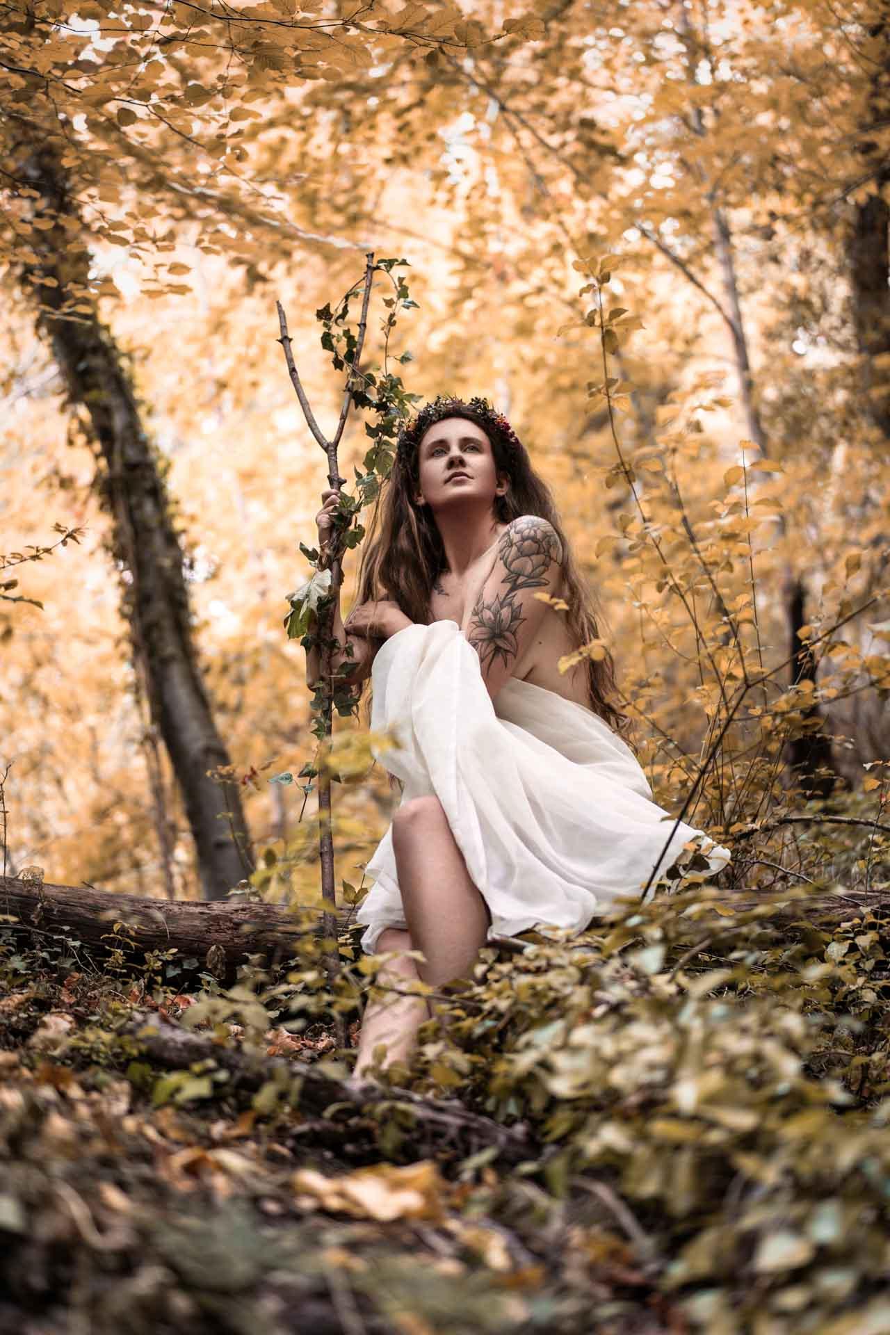 Anaïs se tient assise dans la forêt, le regard déterminé. Un bâton planté dans la terre.