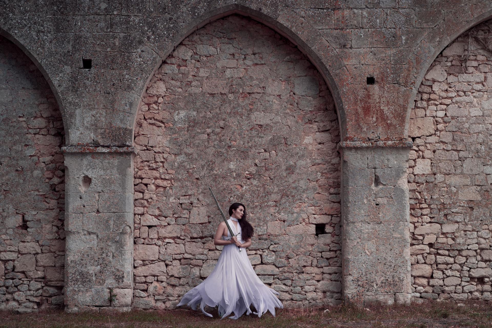 Hélène se tient devant le mur d'une ancienne chapelle depuis longtemps oubliée. Elle protège les lieux de son épée.