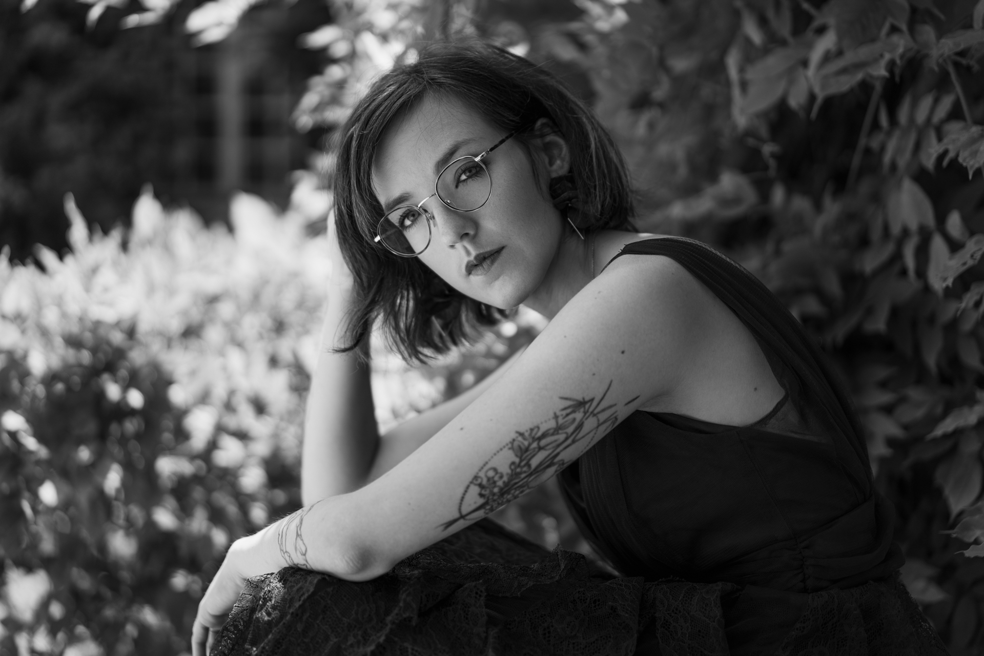 Portrait noir et blanc d'une jeune femme assise dans un jardin