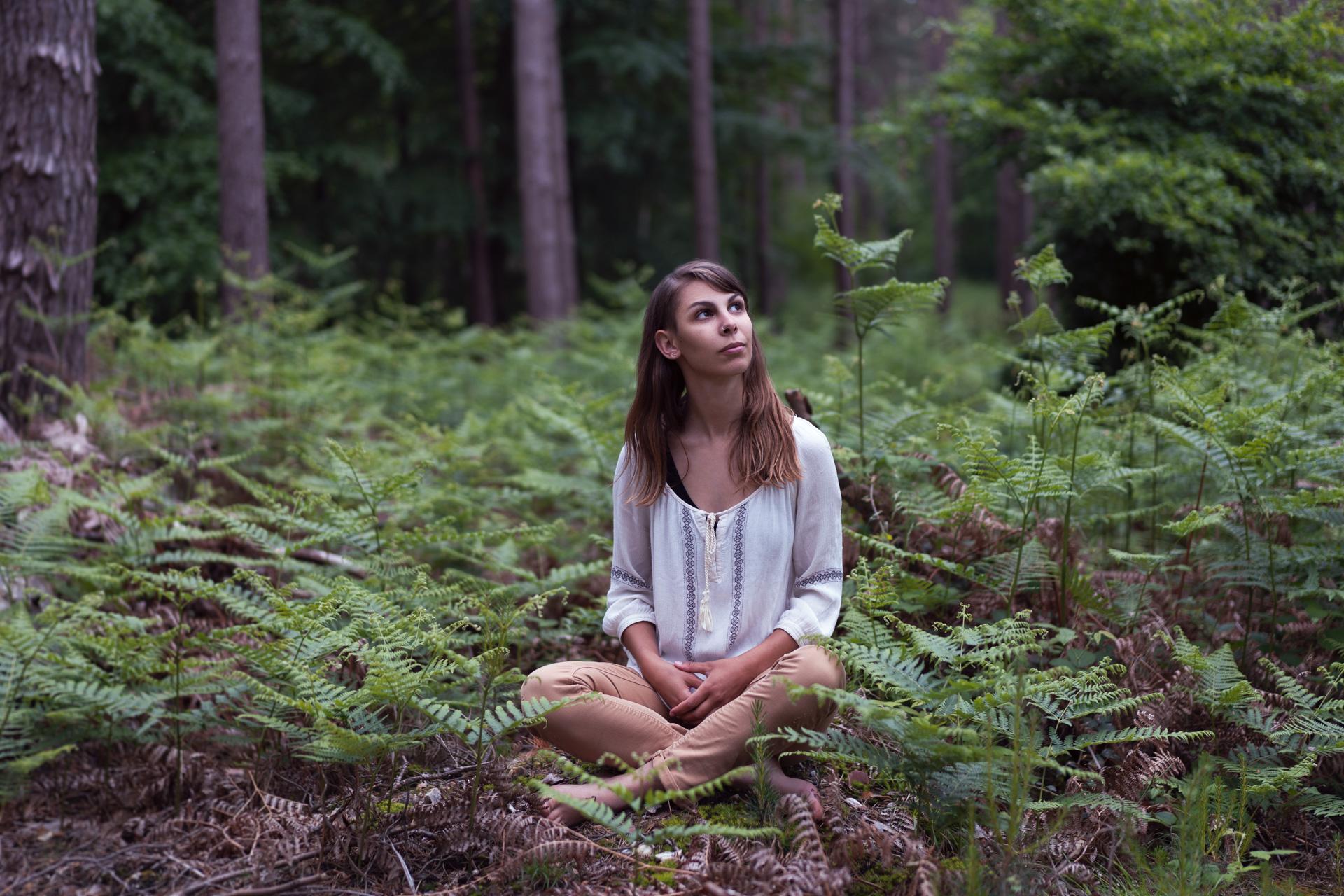 Portrait d'une jeune femme assise dans la forêt